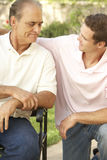 Senior Man Having Serious Conversation Adult Son. In Garden Stock Photo