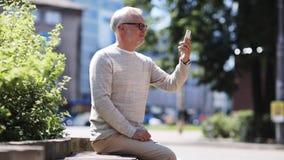 Senior man having video call on smartphone in city stock footage