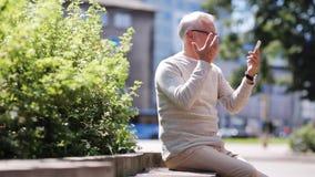 Senior man having video call on smartphone in city stock video footage
