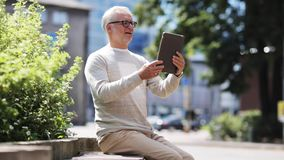 Senior man having video call on tablet pc in city stock footage