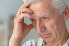 Portrait of senior man with headache holding hands on head stock photo