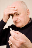 Senior man with headache holding tablet or pill Royalty Free Stock Images