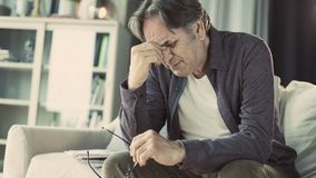 Senior man with headache at home royalty free stock photos