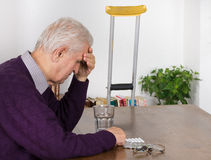 Senior man with headache. Old man with headache sitting at table and has medications on table Royalty Free Stock Photos