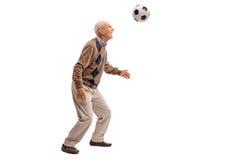 Senior man heading a football stock photo