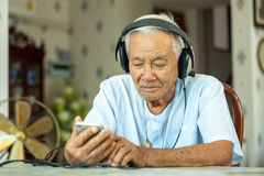 Senior man Headphones Listening Music at home. Happy asian senior man Headphones Listening Music at home Royalty Free Stock Photography