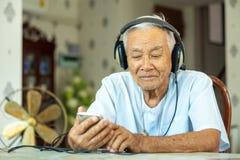 Senior man Headphones Listening Music at home. Happy asian senior man Headphones Listening Music at home Royalty Free Stock Photos