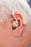Senior Man With Hearing Aid. Closeup of senior man with hearing aid behind the ear Royalty Free Stock Photography