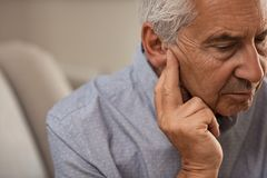 Senior man with hearing problems. Side view of senior man with symptom of hearing loss. Mature man sitting on couch with fingers near ear suffering pain stock image