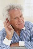 Senior man with hearing trouble. Portrait of  senior man,  hard of hearing, placing hand on ear asking someone to speak up Royalty Free Stock Photos