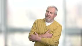 Senior man with heart attack. Unhappy mature man clutching his chest on blurred background. Heart problem concept stock footage