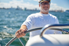 Senior man at helm on boat or yacht sailing in sea Royalty Free Stock Photography