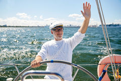 Senior man at helm on boat or yacht sailing in sea Stock Image