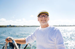 Senior man at helm on boat or yacht sailing in sea. Sailing, age, tourism, travel and people concept - happy senior man in captain hat on steering wheel and royalty free stock photos