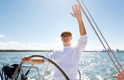Senior man at helm on boat or yacht sailing in sea Royalty Free Stock Photos