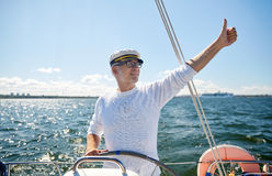 Senior man at helm on boat or yacht sailing in sea. Sailing, age, tourism, travel and people concept - happy senior man in captain hat on steering wheel and royalty free stock photo