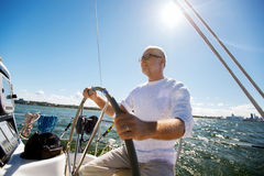 Senior man at helm on boat or yacht sailing in sea. Sailing, age, tourism, travel and people concept - happy senior man in captain hat on steering wheel and royalty free stock photography