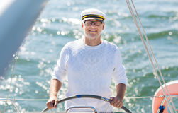 Senior man at helm on boat or yacht sailing in sea. Sailing, age, tourism, travel and people concept - happy senior man in captain hat on steering wheel and stock photography