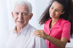 Senior man and helping hand. Senior happy elegant men and young pretty caregiver holding hand on man's arm Royalty Free Stock Photos