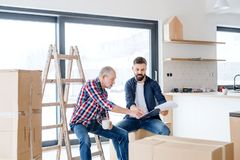 A senior man helping his son with furnishing new house, a new home concept. A cheerful senior men helping his mature son with furnishing new house, a new home stock images