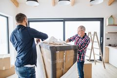 A senior man helping his son with furnishing new house, a new home concept. A cheerful senior men helping his mature son with furnishing new house, a new home royalty free stock photography