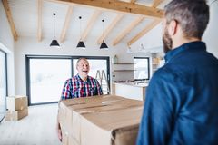 A senior man helping his son with furnishing new house, a new home concept. A cheerful senior men helping his mature son with furnishing new house, a new home royalty free stock images