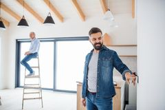 A senior man helping his son with furnishing new house, a new home concept. A cheerful senior men helping his mature son with furnishing new house, a new home stock photography
