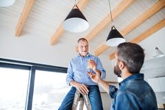 A senior man helping his son with furnishing new house, a new home concept. A cheerful senior men helping his mature son with furnishing new house, a new home stock image
