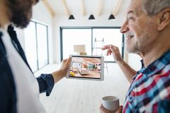 A senior man helping his son with furnishing new house, a new home concept. A cheerful senior men with tablet helping his mature son with furnishing new house royalty free stock photography