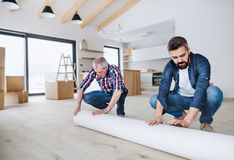 A senior man helping his son with furnishing new house, a new home concept. stock photos