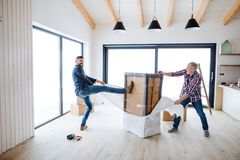 A senior man helping his son with furnishing new house, a new home concept. stock photography
