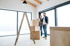 A senior man helping his son with furnishing new house, a new home concept. A cheerful senior men with tablet helping his mature son with furnishing new house stock photos