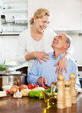 Senior man helping his wife in the kitchen Royalty Free Stock Photos