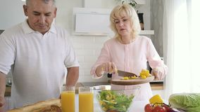 Senior man helping mature wife putting cut pepper to salad bowl. stock video footage