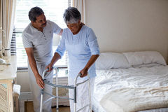 Senior man helping senior woman to walk with walker Royalty Free Stock Image