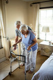 Senior man helping woman to walk with a walker. At home Royalty Free Stock Photo