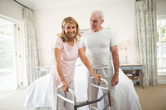 Senior man helping woman to walk with walker Royalty Free Stock Images