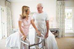Senior man helping woman to walk with walker Royalty Free Stock Photos