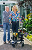 Senior Man Helping Woman with Walker Outdoors. Senior Man Helping Blond Woman with Walker Walking Outdoors in front of Retirement Community Building on Sunny Day Royalty Free Stock Image
