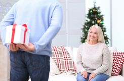 Senior man hiding Christmas present for his  wife at home. Senior men hiding Christmas present for his wife at home Royalty Free Stock Photo