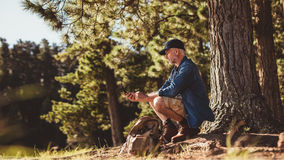 Senior man on hike in nature using a compass Royalty Free Stock Photo