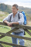 Senior Man Hiking In Countryside Resting By Gate Royalty Free Stock Photos