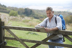 Senior Man Hiking In Countryside Resting By Gate Stock Images