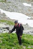 Senior man hiking into the mountains Stock Image