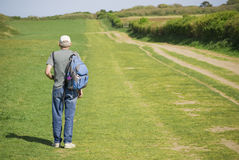 Senior man hiking over field in summer Stock Photography