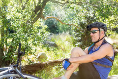 Senior man is on his bike in a forest Royalty Free Stock Photography