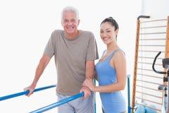 Senior man and his coach smiling at camera Stock Image