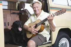 Senior Man With His Dog Playing Guitar In Campervan. Portrait of a happy senior men sits in his campervan with a guitar and his pet dog royalty free stock photo