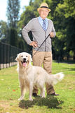 Senior man and his dog posing in the park Royalty Free Stock Photography