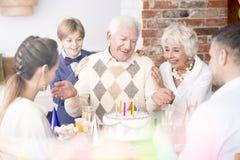 Senior man and his family at birthday party. Happy senior men and his family having fun at birthday party Royalty Free Stock Photos